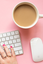 Female entrepreneur's hands with hot pink nail polish typing on keyboard with a mouse and coffee cup on pretty pink background.