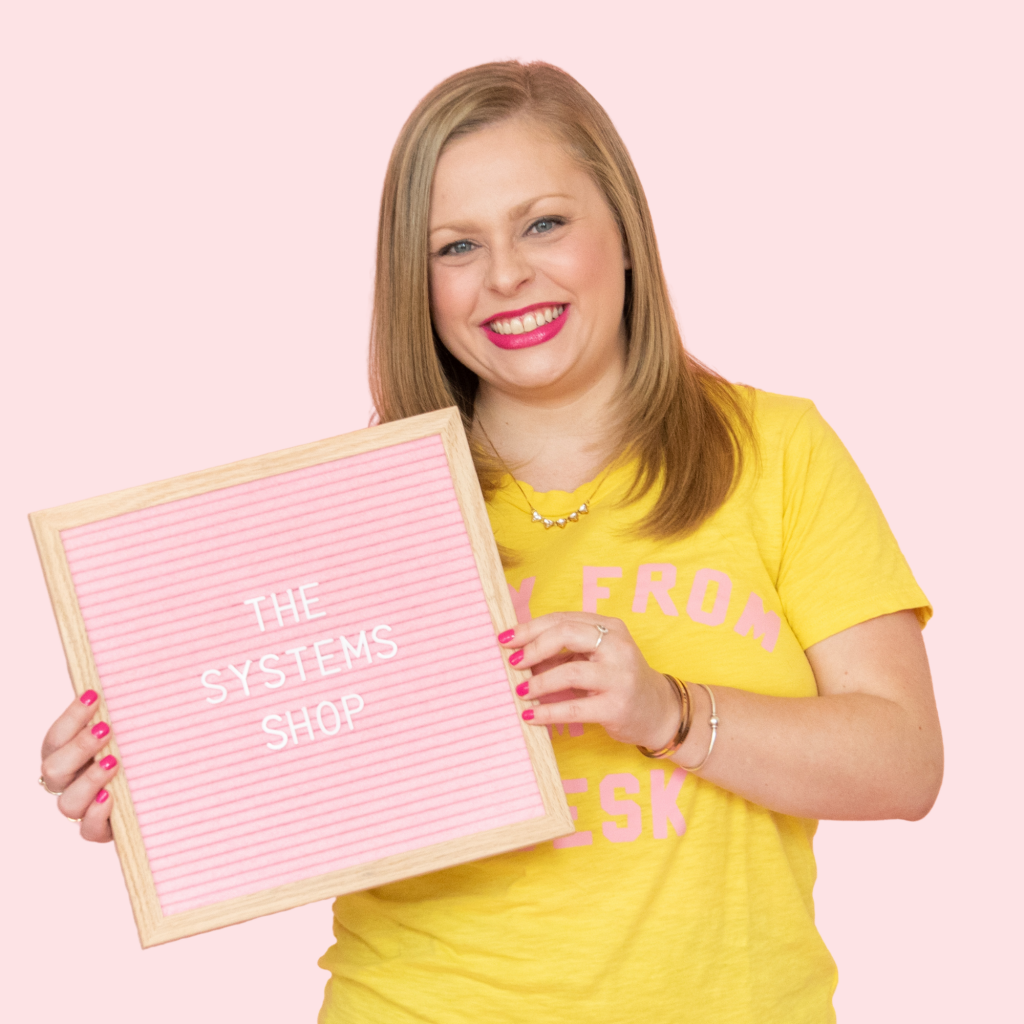 Alexandra of The Productivity Zone holding a pink letterboard with the words The Systems Shop spelled out on it