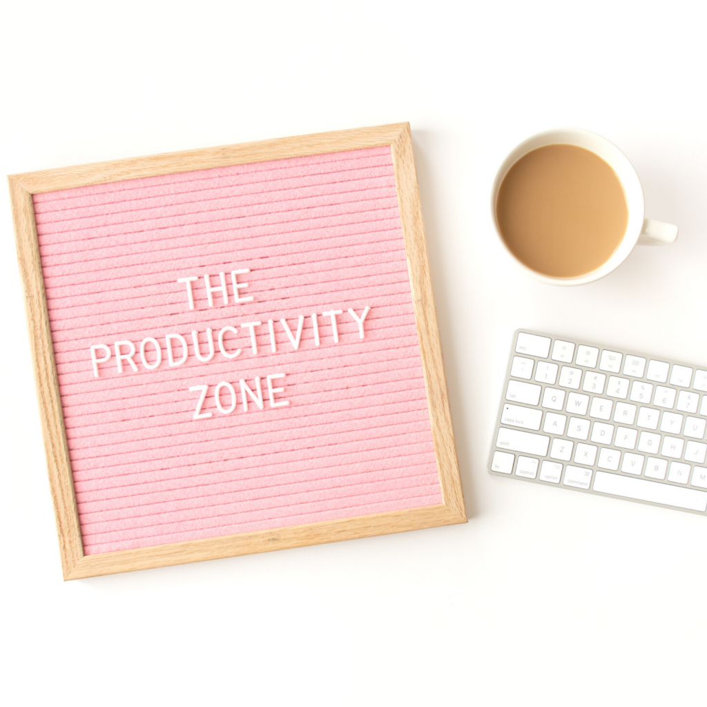 The Productivity Zone spelled out on pink letterboard with coffee cup and keyboard