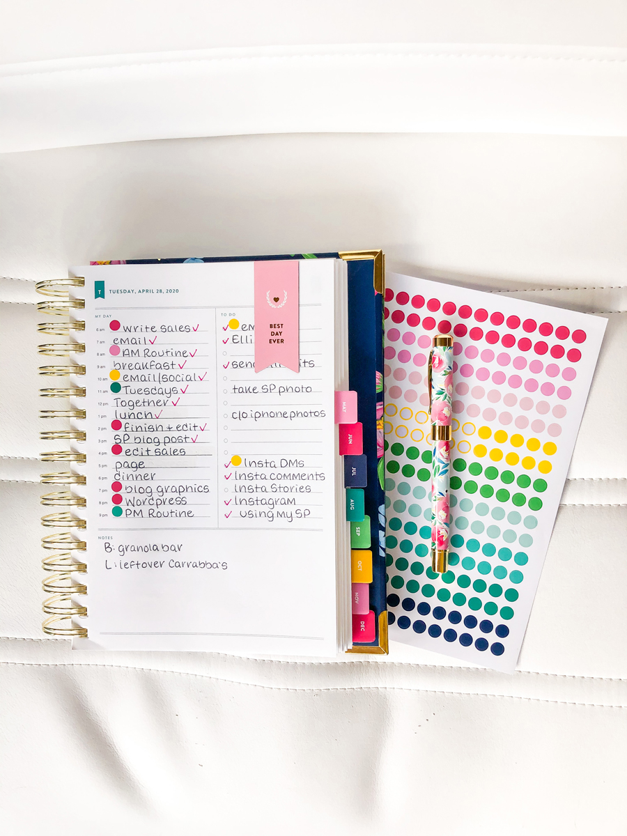 Daily Simplified Planner laying open with a sheet of color-coding stickers and happy floral pen