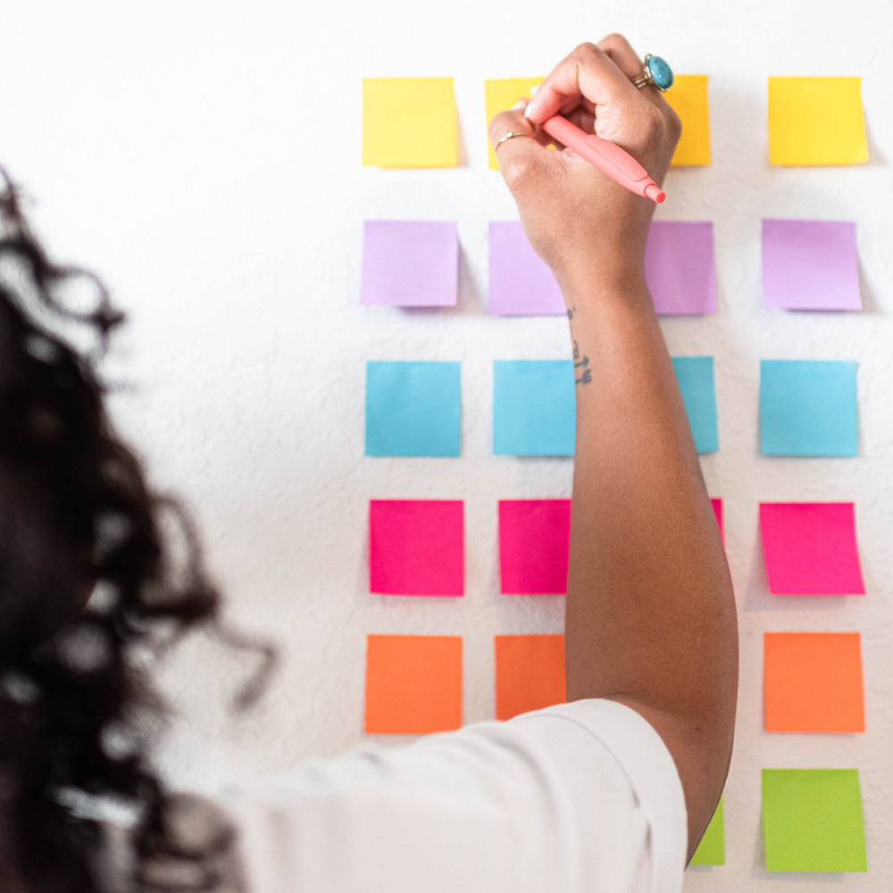 Black girl writing on colorful post-its that are stuck to a white wall.