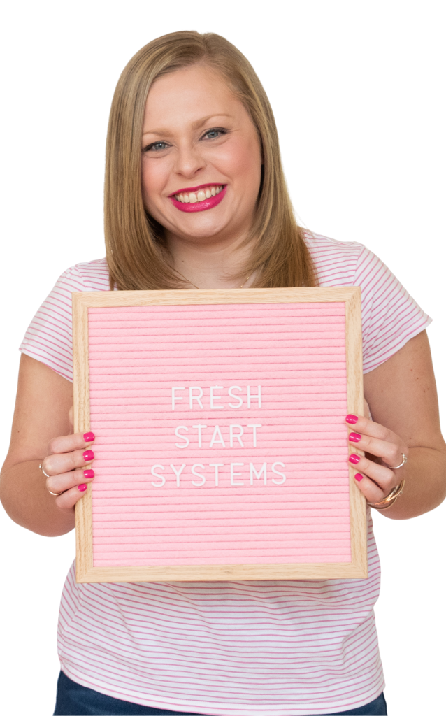 Alexandra of The Productivity Zone holding a pink letterboard with the words Fresh Start Systems spelled out on it.