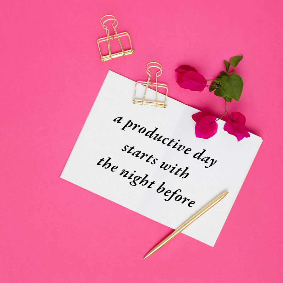 """White notecard with the words """"a productive day starts with the night before"""" typed out on it laying on a hot pink background surrounded by a gold pen and gold binder clips."""