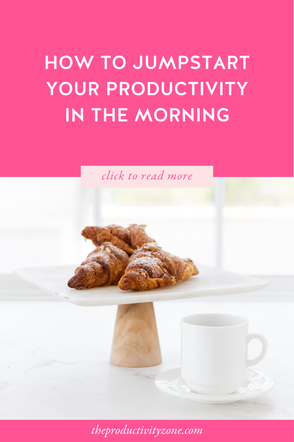 Chocolate croissants on a platter with a wooden pedestal beside a white coffee cup and saucer on a marble counter in front of a brightly lit window