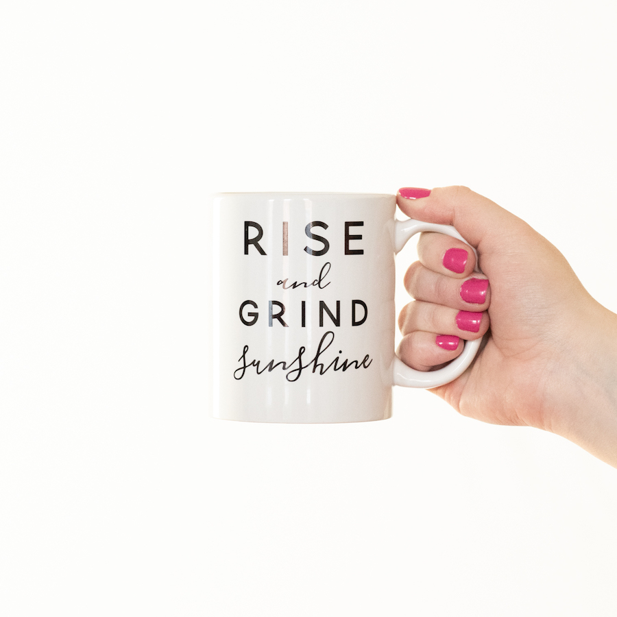White coffee mug with RISE and GRIND sunshine printed on it in black bold and cursive letters