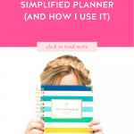 Blonde woman holding a daily Happy Stripe Simplified Planner in front of her face