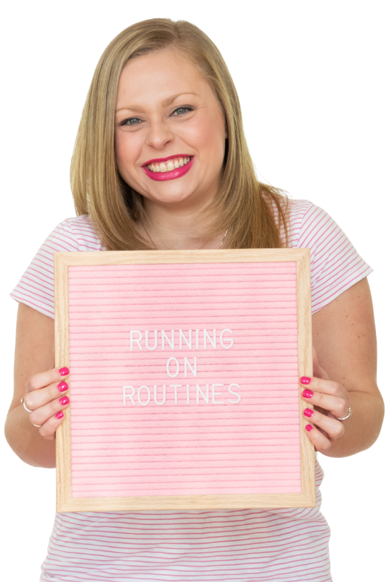 Alexandra of The Productivity Zone holding a pink letterboard with the words Running on Routines spelled out on it.