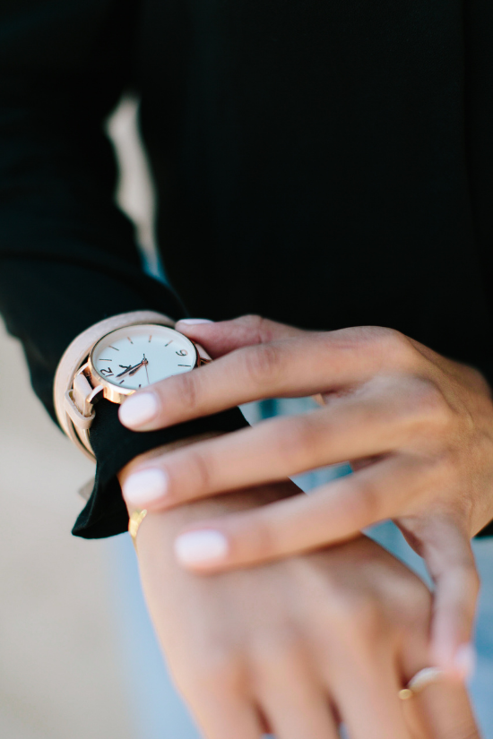 White woman wearing a black shirt checking the time on her blush pink double strap watch.