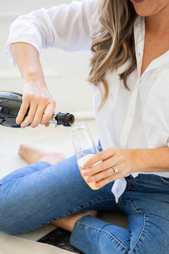 White woman wearing jeans and a white blouse sitting on the floor pouring champagne into a glass.